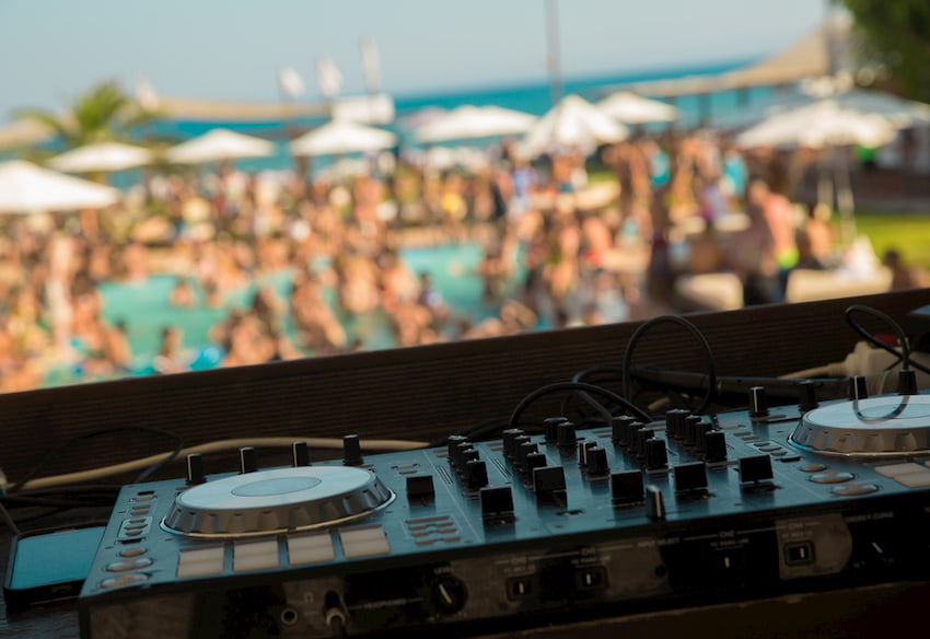 a DJ booth leads a pool party while attendees dance near the water