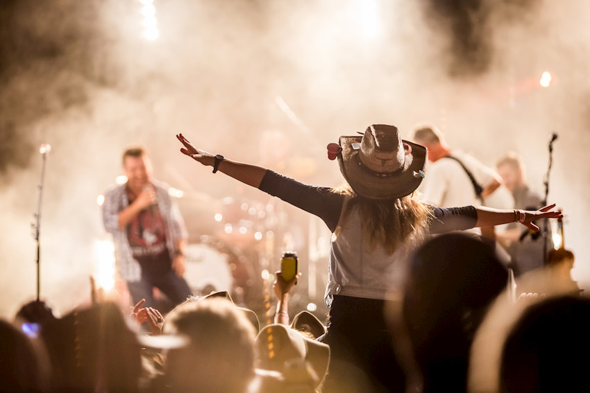 girl wearing a cowboy hat cheers on a country music performer at Stagecoach Festival