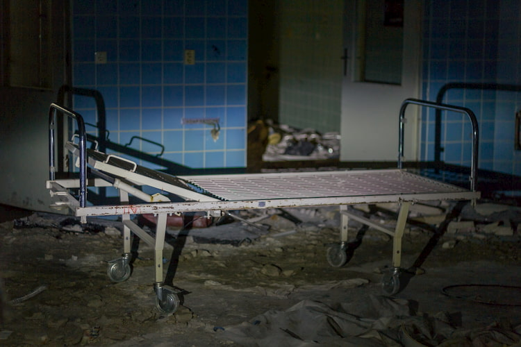 Abandoned hospital bed in dark room