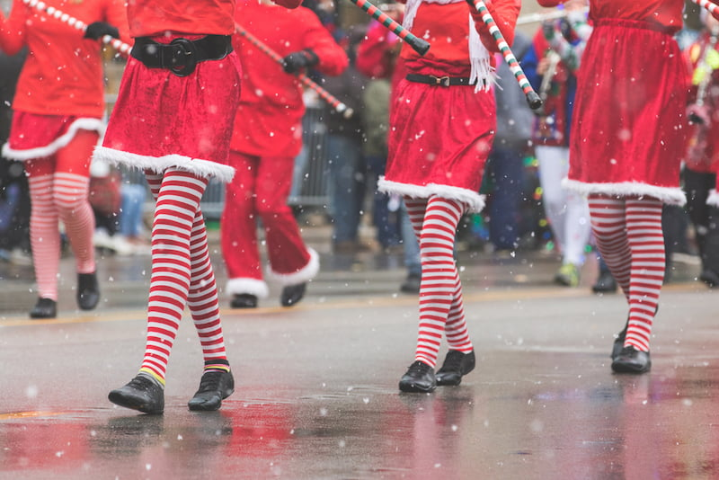 parade performers in red and white striped tights march through los angeles at the hollywood christmas parade