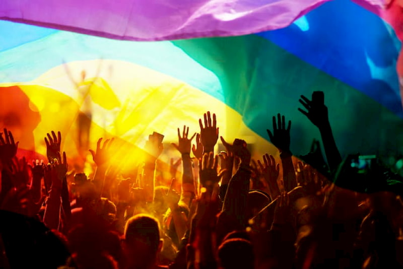 friends hold up their hands during a concert at LA Pride. a rainbow flag waves in the foreground
