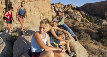 A group of women enjoy the view while hiking through Joshua Tree National Park