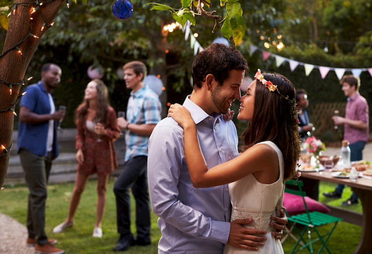 Bride and groom kissing in casual wedding attire at outdoor wedding