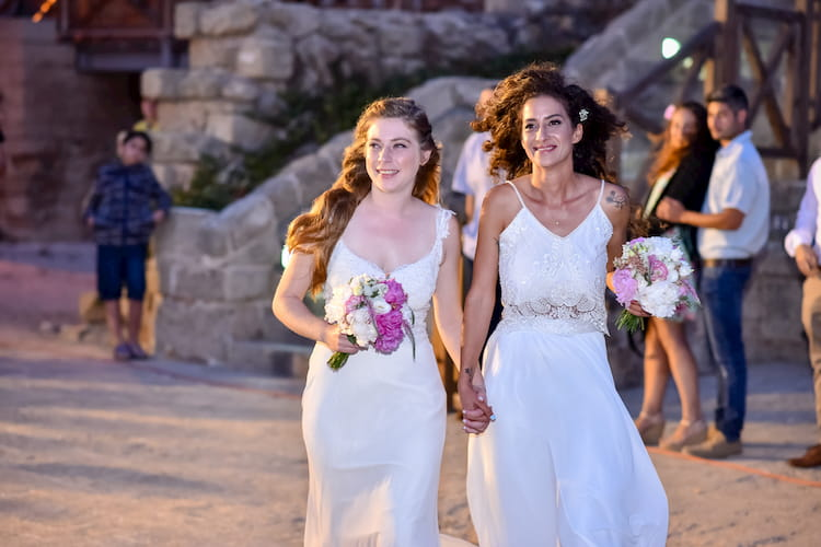 Two brides carrying flowers as they walk down aisle outside
