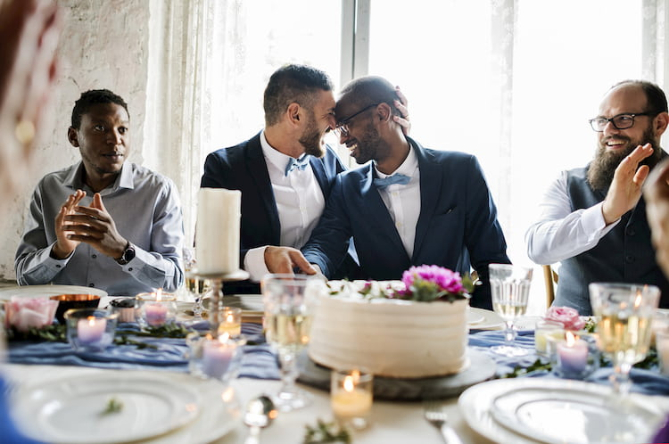 Two grooms kissing at table with wedding cake and guests