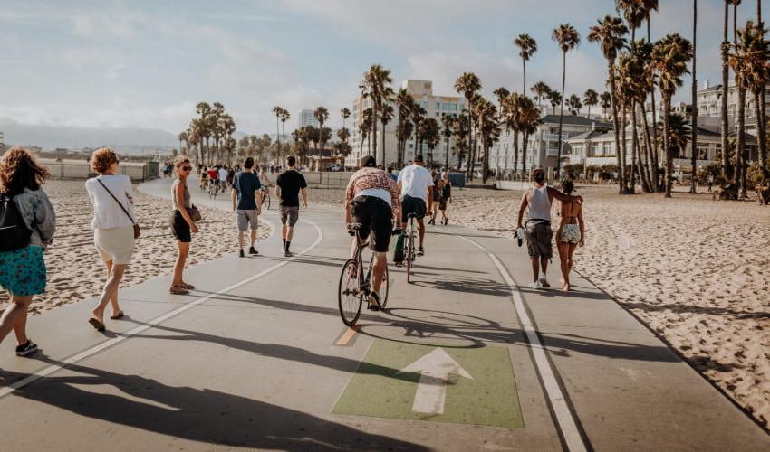 Pedestrians bike and walk on the beach in Venice, California
