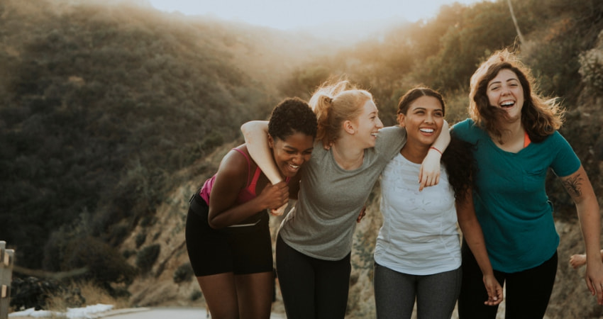 A group of women laugh as they hike up Mount Baldy