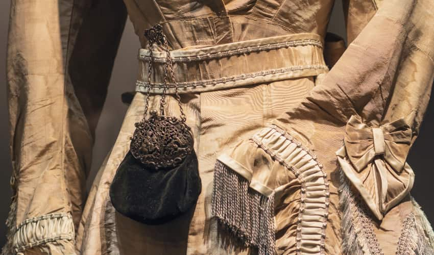 a century-old-dress and purse rest on a mannequin in a museum