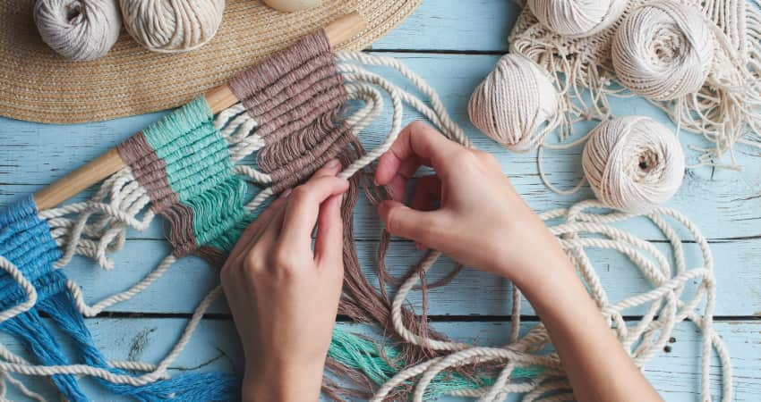 a crafter makes a wall-hanging out of rope and twine