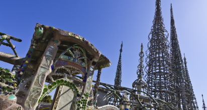 the gateway of the Watts Towers, with the tallest spires rising up in the distance