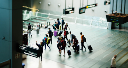 a large group of people with suitcases walk through an airport toward a gate