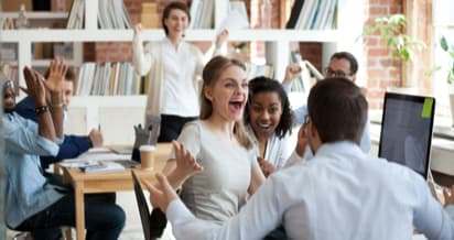 A group of colleagues cheering in the office