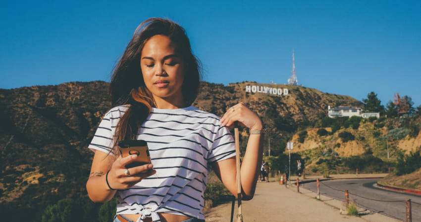 A woman texts on her phone with the Hollywood sign in the background