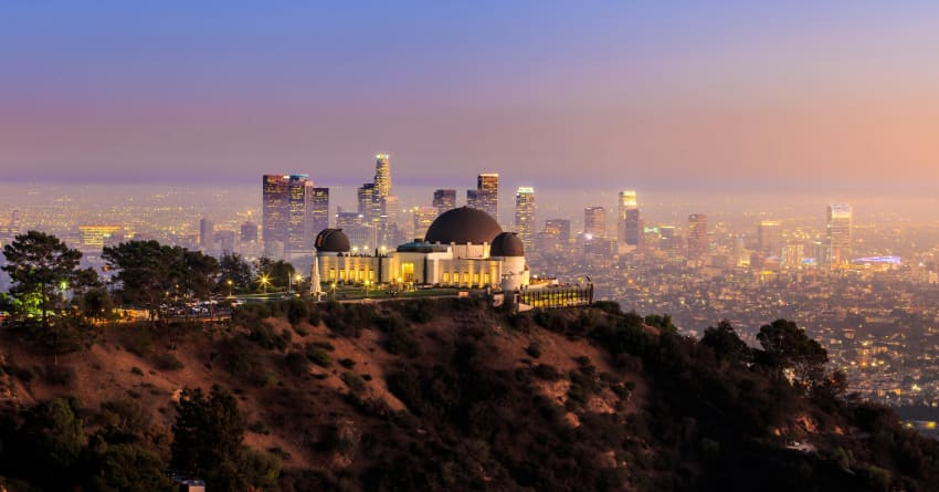 The Griffith Observatory at sunset, the Los Angeles skyline in the distance