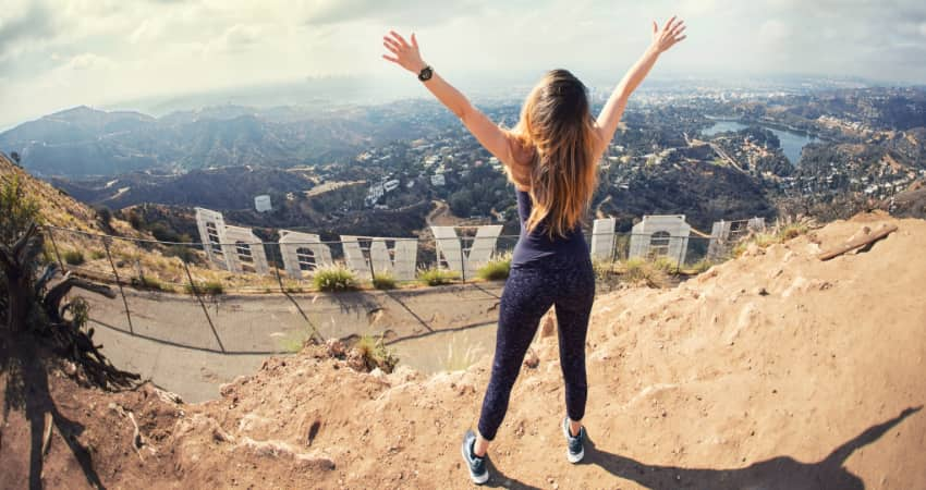 A woman stands on the peak behind the Hollywood sign with arms outstretched