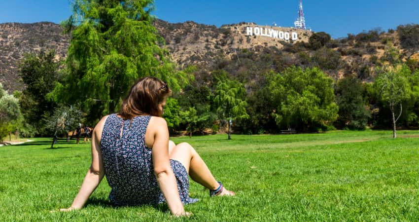 A woman sits on the grass in a park underneath the Hollywood sign