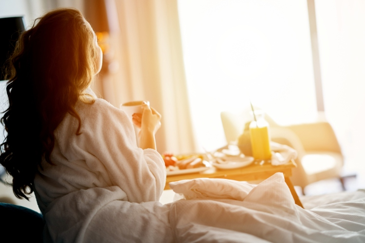 A girl sitting on a hotel bed sipping a drink and staring at the early morning sunshine