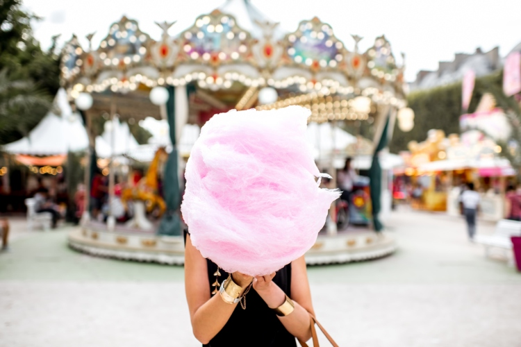 A person is posing with pink cotton candy