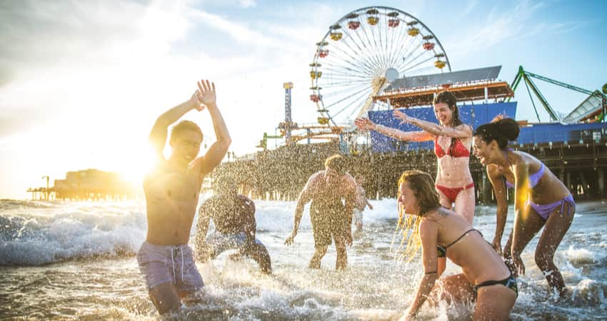 A group of people splashing in the water on the beach with the Santa Monica Pier in the background