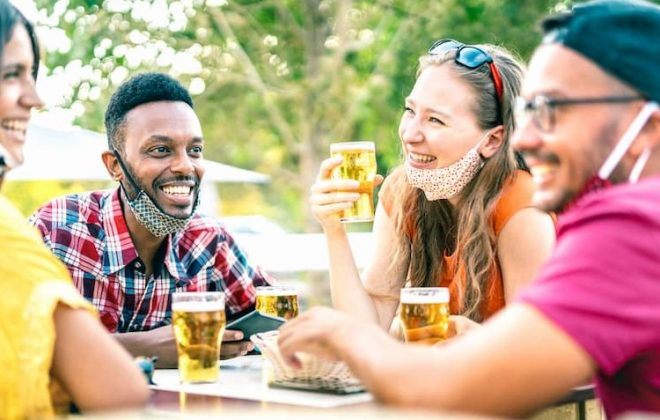 Friends drinking outside with face masks lowered