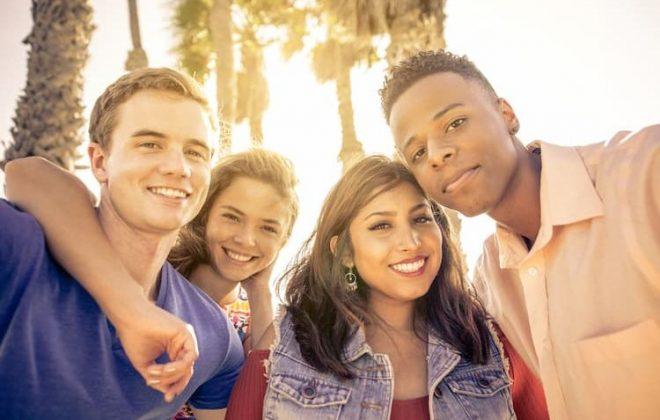 Four friends outside in LA near palm trees