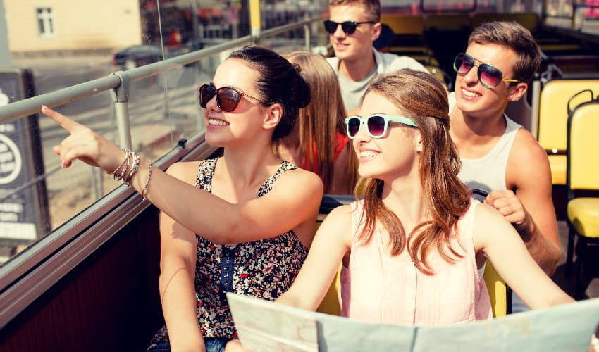 A group of sightseers hold a map and point at attraction while riding on a private bus rental