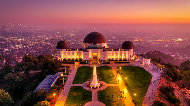 an aerial view of the observatory's front lawn complex and building, at dusk, with los angeles in the background