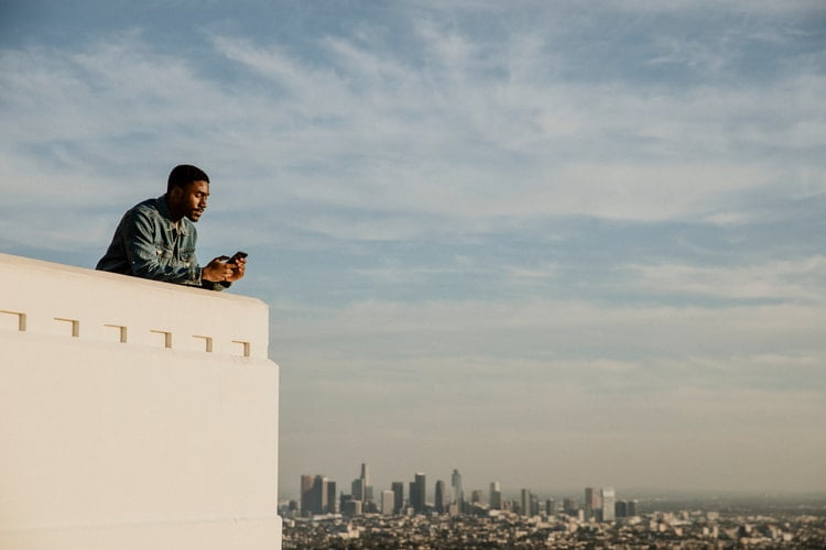 a man leans on the edge of a high observatory point and looks at his phone