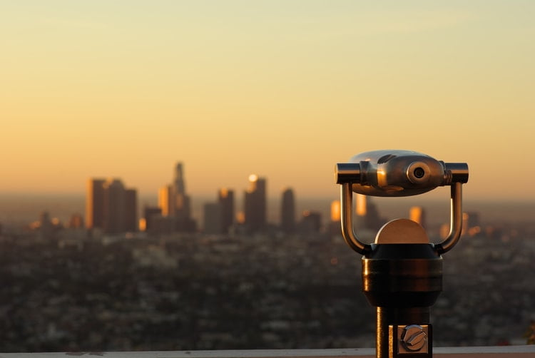 a telescope looking over a city center at dusk