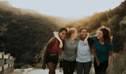 A group of friends smiling and hugging on a beach