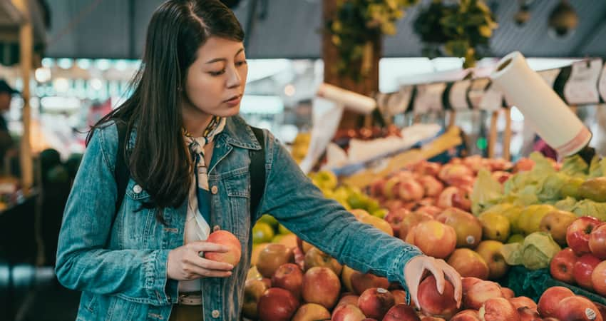 A woman picking out produce at a farmer's market
