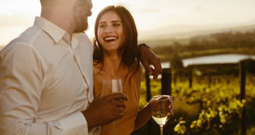 A couple smiling and drinking white wine in front of a vineyard