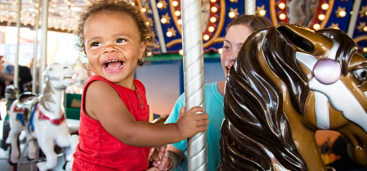 a child smiles while sitting on a horse on a carousel