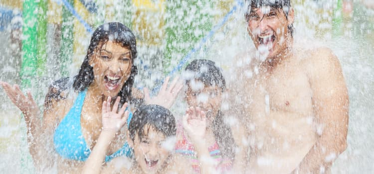 a family gets soaked in the middle of a water park fountain