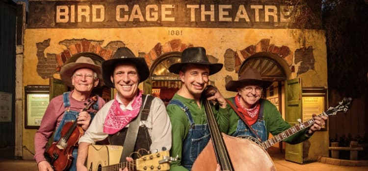 """a band dressed in cowboy hats and overalls holds their instruments in front of a stage with a sign that reads """"bird cage theatre"""""""