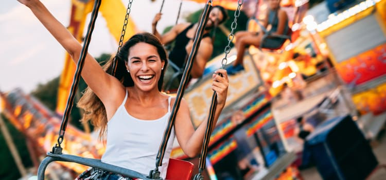 woman smiles and holds up her arm while riding on a chairswing above a theme park