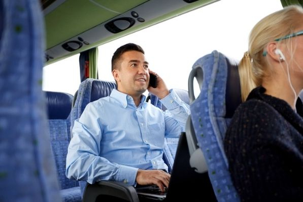 professional man talks on phone and works on computer while on a charter bus