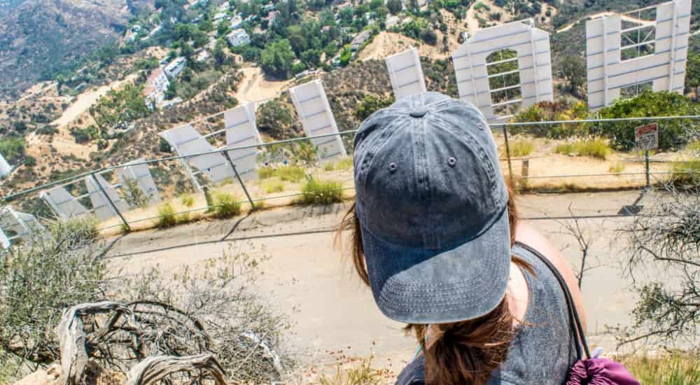 A sightseer looks out across the Los Angeles cityscape from behind the Hollywood sign