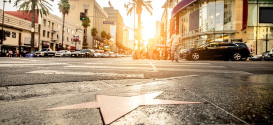 the hollywood walk of fame with cars and tourists