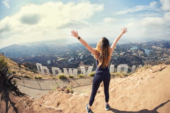 woman stands in front of hollywood sign in los angeles
